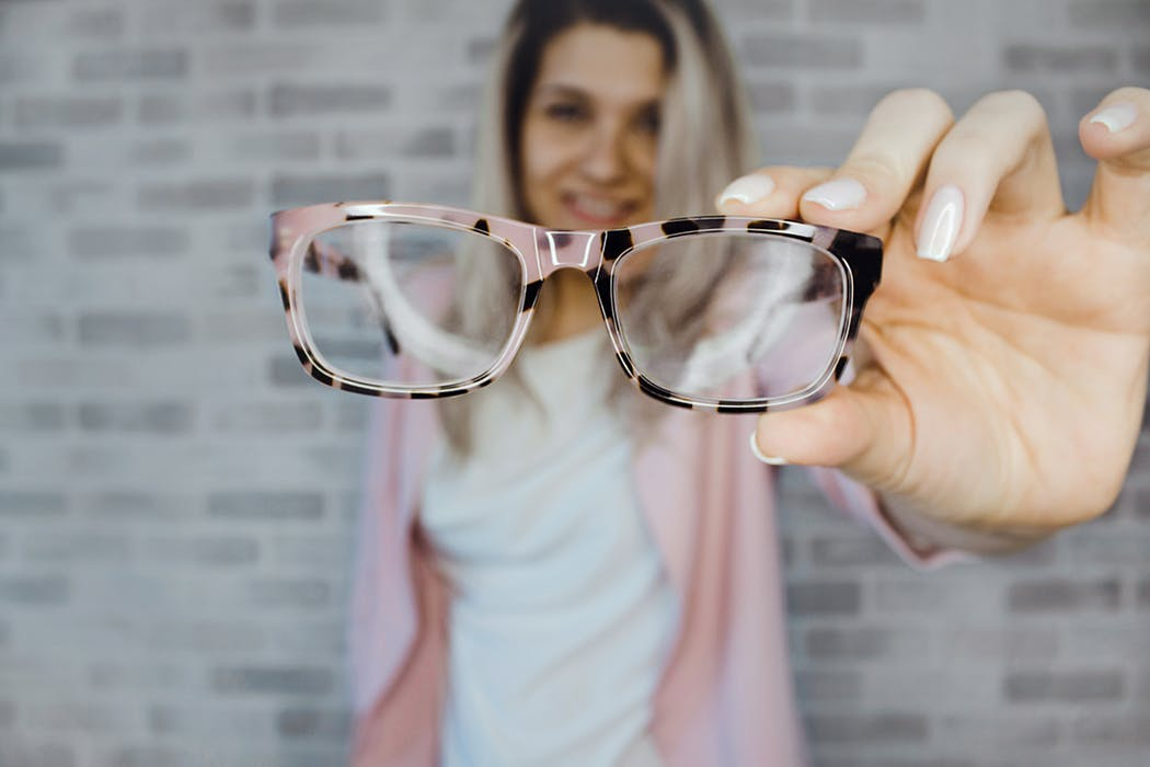 woman holding a stylish glasses bought online