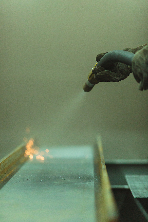 An employee prepares a metal part for painting through abrasive blast