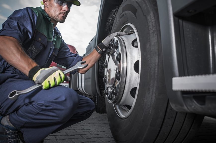 Mechanic while using portable truck tire changer